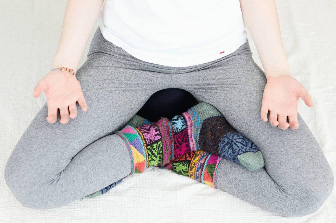 Meditationssitz mit bunten Socken und Händen auf den Oberschenkeln