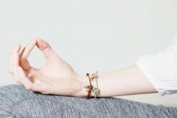 Hand liegt beim Meditieren auf Oberschenkel.